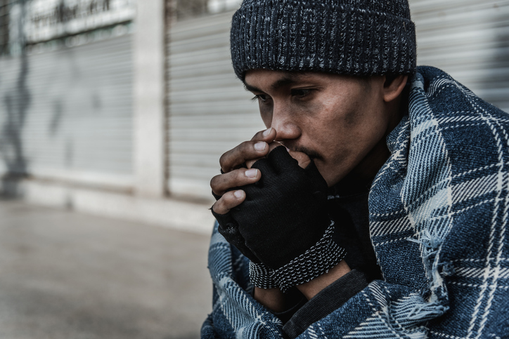 person experiencing homelessness blowing on hands to keep warm