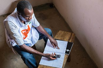A worker reports indoor residual spraying data through a cell phone. Abt Associates is implementing the PMI AIRS project, which has protected more than 2.6 million people in Zambia from malaria. Photo credit: Abt Associates