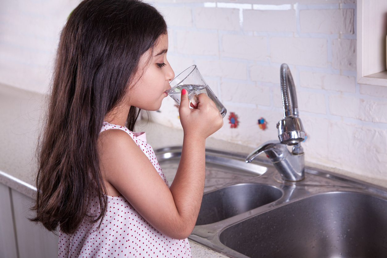 girl drinking water at sink