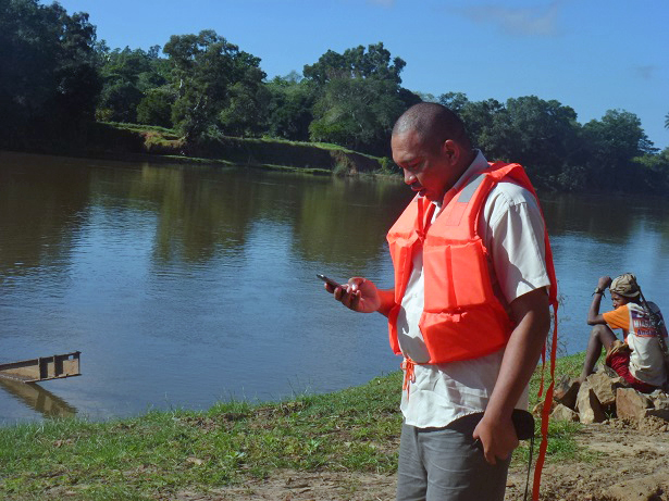 Environmental Compliance Officer Tahina Masihelison uses a smartphone to record a river crossing. Photo credit: Mijoro Rasolofomalala