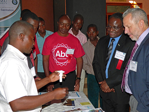 A SHOPS-trained mason (L) describes the project's new transitional latrine design using a 3D printed model. On the right are Dr. Charles Mwansambo, chief of health services for the Ministry of Health, and Peter Halpert, health office chief for USAID/Malawi.
